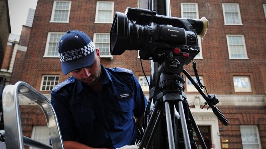 A police officer inspects a lamppost outside the Lindo Wing of Saint Mary's Hospital in London, on July 12, 2013, where Prince William and his wife Catherine's baby will be born. The media frenzy over the birth reached fever pitch as the reported due date came and went with no sign of the royal heir.