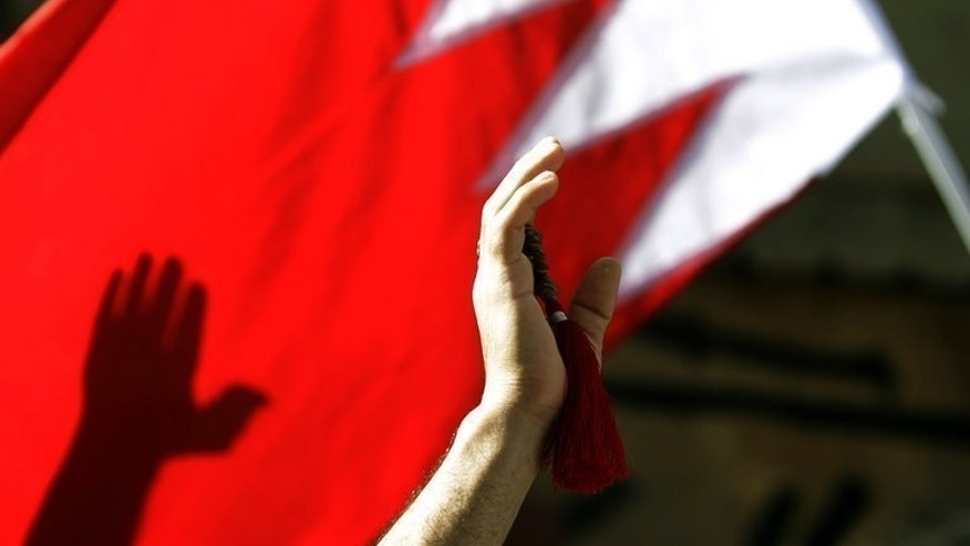 "A Shiite protester waves a Bahrain flag during a rally in Manama, on March 22, 2011. The authorities in Bahrain have warned people not to join protests planned for next month by a new opposition campaign named after Egypt's ""Tamarod"" opposition movement."