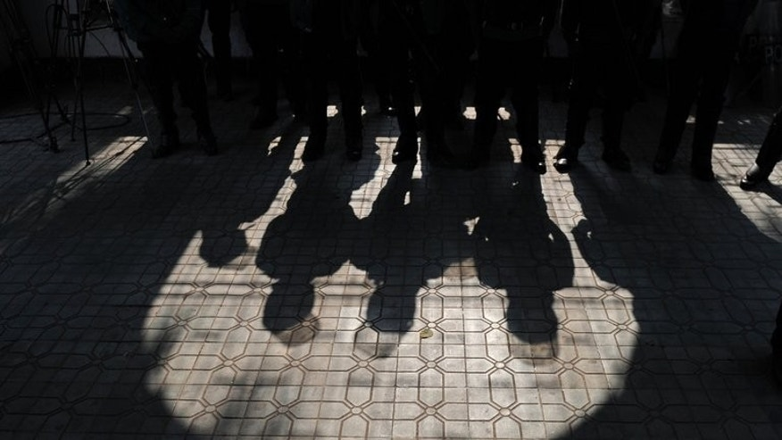 The shadows of Bangladeshi riot-police are seen as they guard the International Crimes Tribunal in Dhaka, on January 21, 2013. Clashes have erupted in Bangladesh between police and supporters of the country's biggest Islamic party ahead of a court verdict against a top Islamist for allegedly masterminding atrocities during the 1971 liberation war against Pakistan.