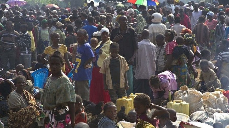 Refugees from the Democratic Republic of Congo wait after crossing into western Uganda at the Busunga border post on July 13, 2013. More than 55,000 people have arrived in Uganda after fleeing a rebel attack, Red Cross officials say, a dramatic rise from earlier estimates.
