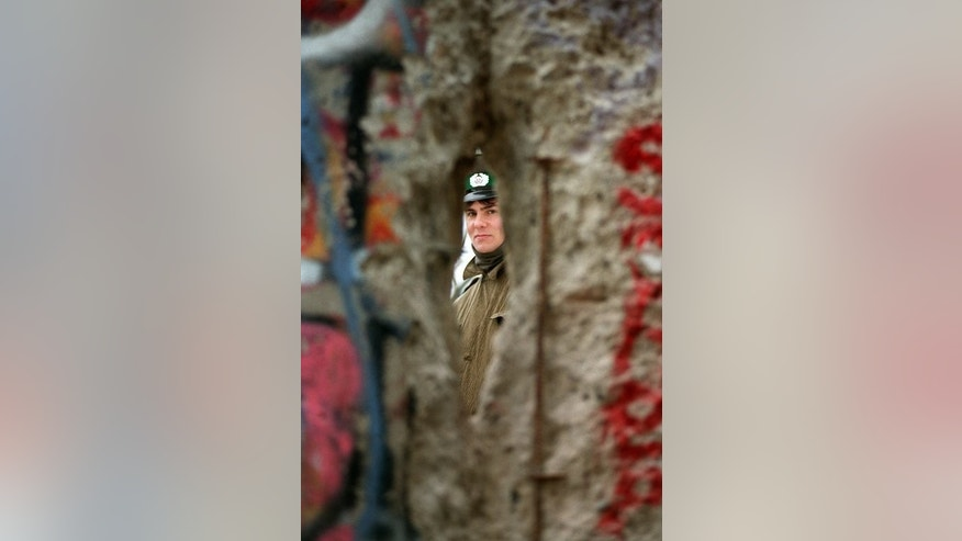 An East German policeman looks through a gap in the Berlin Wall, on November 21, 1989. Twenty-five years ago this week, US rock legend Bruce Springsteen played to an estimated 300,000 East Germans thirsting for freedom, a spectacular event that some now argue may have helped topple the Berlin Wall.