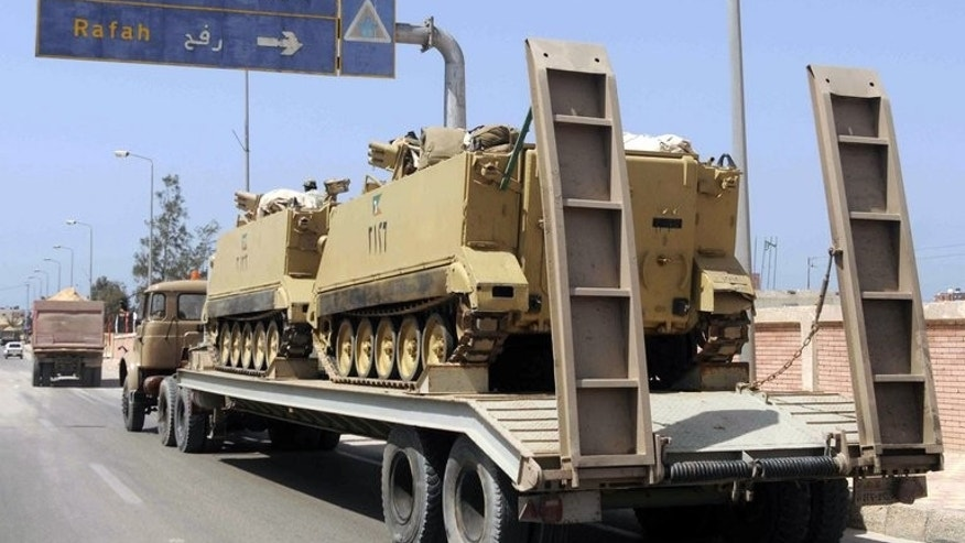 An Egyptian military truck carries armoured personnel carriers towards Al-Arish, in the northern Sinai on May 20, 2013. Militants killed at least three people Monday and wounded 17 when they fired on a bus carrying workers in Al-Arish, security and medical sources said.