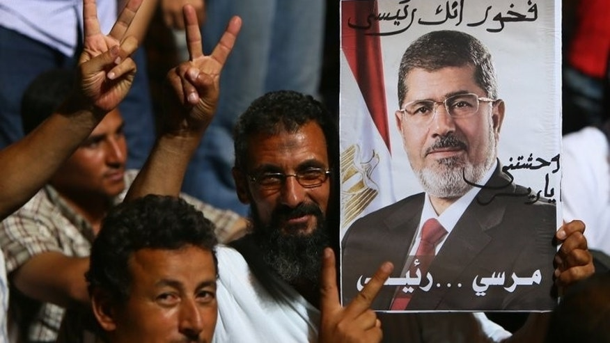 Supporters of deposed Egyptian president Mohamed Morsi flash the victory sign during a rally outside Cairo's Rabaa al-Adawiya mosque on June 10, 2013.