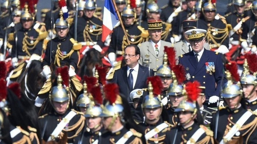 French Army Chief of Staff, Admiral Edouard Guillaud (right) and President Francois Hollande review the troops during the Bastille Day parade on the Champs Elysees in Paris, on July 14, 2013.