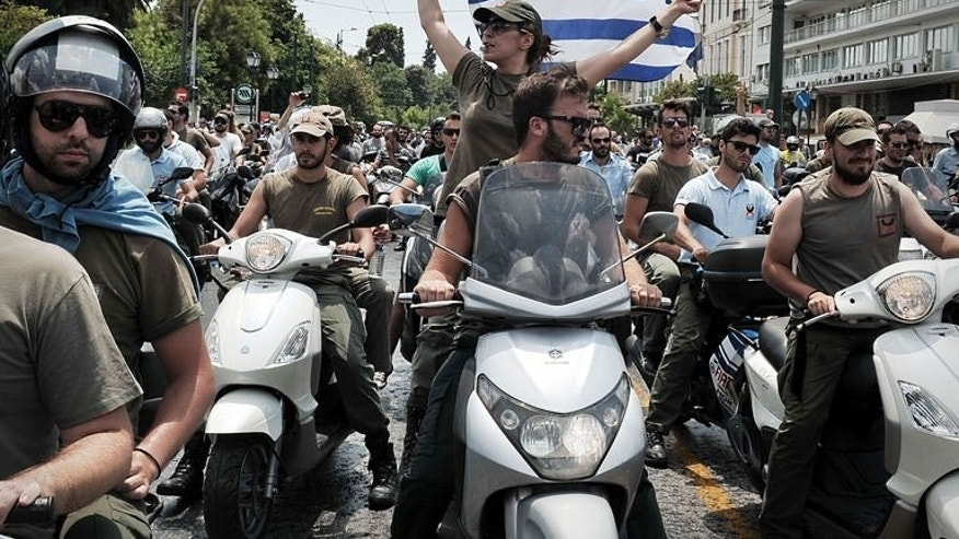 Striking municipal police drive past the Greek parliament in Athens during a protest on July 11, 2013. Greece's prime minister faces protests this week over a bill that must pass for the country to receive a fresh tranche of EU-IMF aid.