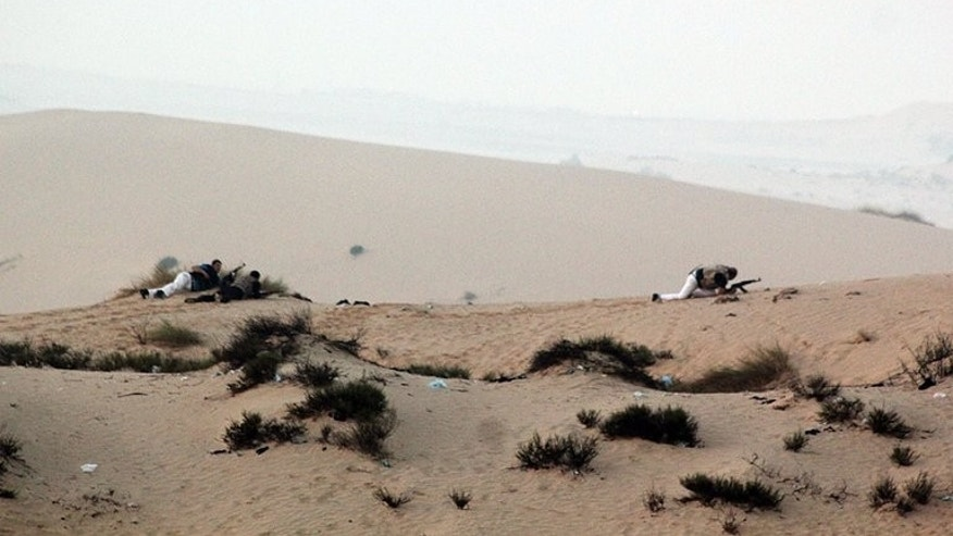 Egyptian security forces take position on a sand dune during an operation in the northern Sinai peninsula on August 8, 2012. Gunmen clashed with the Egyptian army on Sunday near the Israeli border, security sources said, in the latest violence to erupt in the Sinai peninsula since the ouster of president Mohamed Morsi.