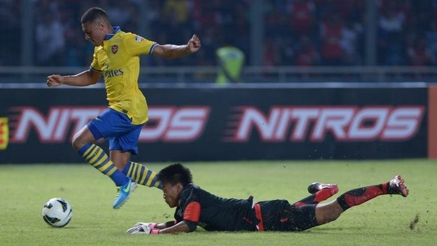 Arsenal's striker Alex Oxlade-Chamberlain (L) vies with Indonesia's goalkeeper Kurnia Meiga during a friendly football match Arsenal FC vs Indonesia Dream Team in Jakarta on July 14, 2013. Arsenal won 7-0.