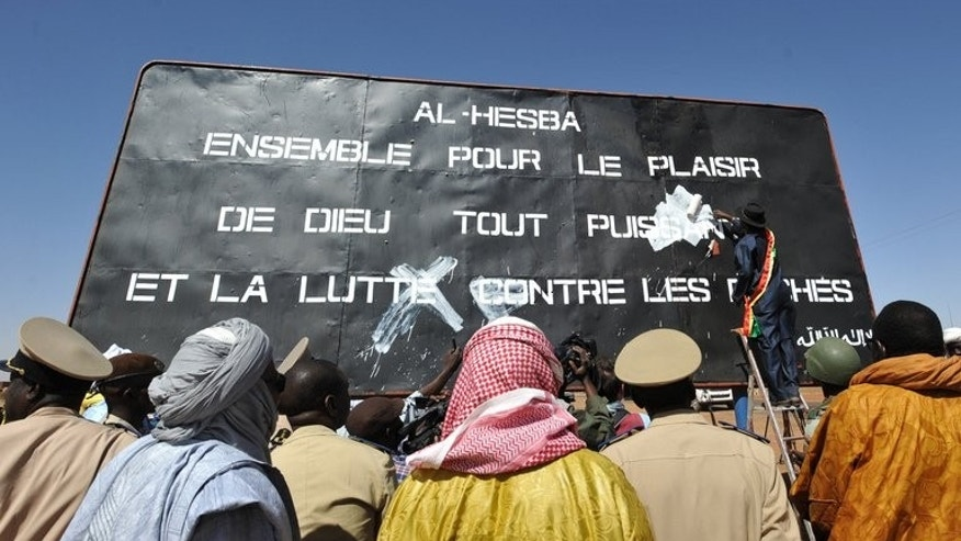 Men watch on January 30, 2013, as the mayor of the Malian city of Gao paints over a billboard left by MUJAO, an offshoot of AQIM. A Mauritanian court on Sunday freed a Canadian jailed for attempting to join an Al-Qaeda training camp in neighbouring Mali, a judicial source said.