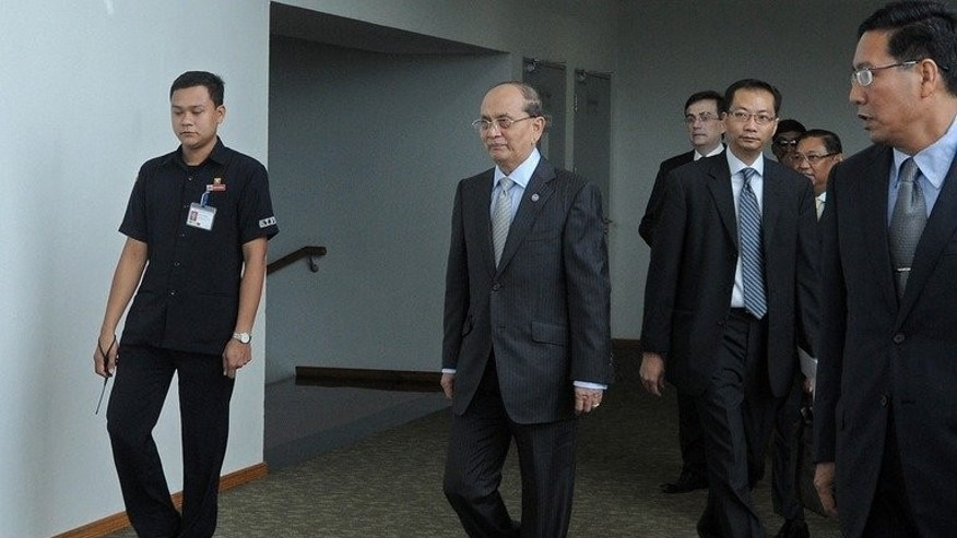 Myanmar President Thein Sein (C) arrives at Yangon International airport before departing for a visit to Britain and France, on July 14, 2013. The former junta general looks to build on support for his much-lauded reforms.