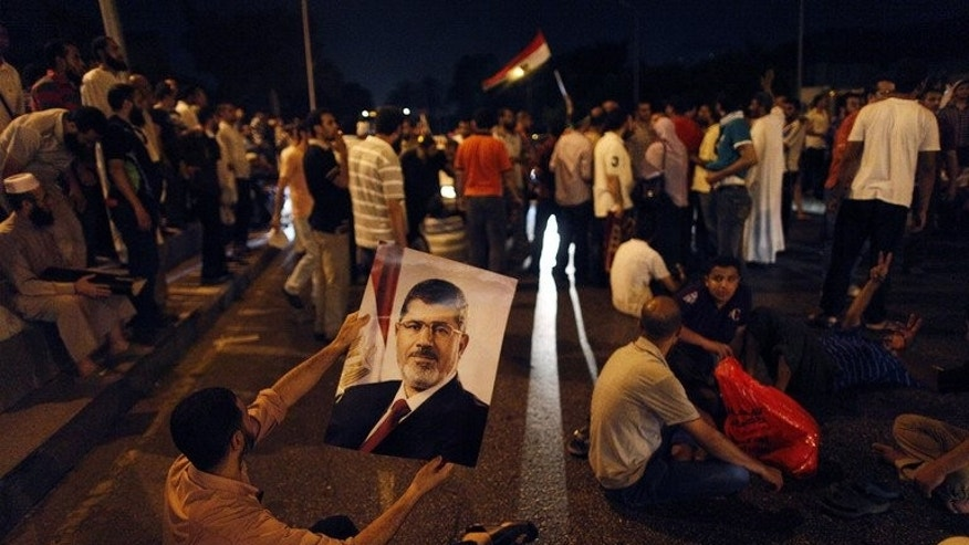 An Egyptian supporter of deposed president Mohamed Morsi holds his portrait during a sit-in protest outside the presidential palace in Cairo on July 13, 2013. Diehard Morsi supporters have been rallying in Cairo for nearly two weeks calling for his reinstatement, but their prolonged protest has left them isolated.
