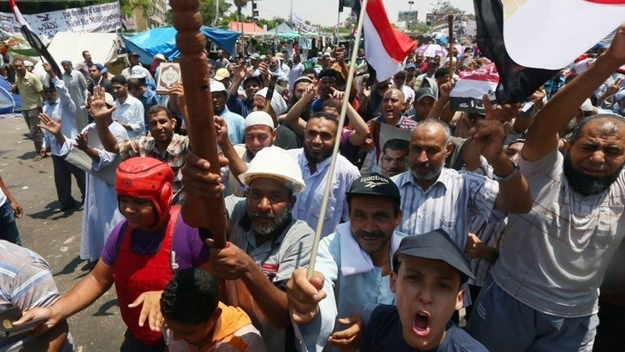 Supporters of Egypt's deposed president Mohamed Morsi chant during a rally outside Cairo's Rabaa al-Adawiya mosque on July 13, 2013.