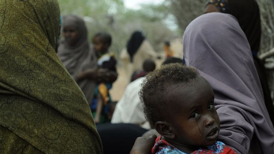 A young Somali refugee waits with her mother to be vaccinated within the Dadaab refugee complex in Kenya's north-east province on August 1, 2011. Many in the Dadaab camp in northeast Kenya are nervous about the growing pressure to leave the camp and return to Somalia some last saw two decades ago.