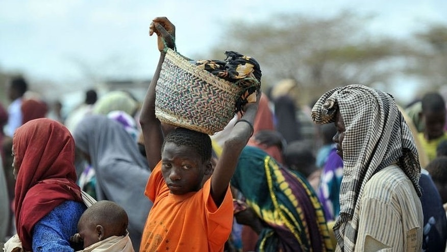 A boy carries his belongings as displaced Somali refugees arrive at the Dadaab camp in eastern Kenya on July 23, 2011. Many in the Dadaab camp in northeast Kenya are nervous about the growing pressure to leave the camp and return to Somalia some last saw two decades ago.