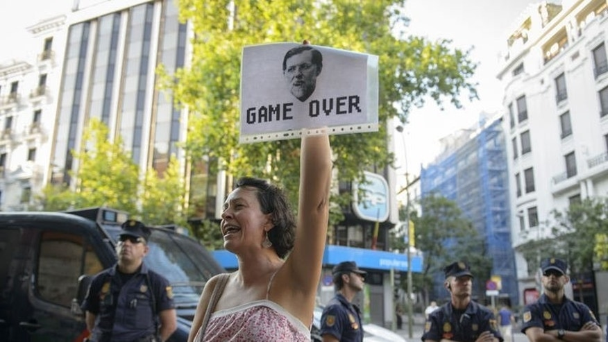 A woman holds a placard depicting Spanish Prime Minister Mariano Rajoy during a demonstration against corruption at the People Party's headquarters in Madrid on July 14, 2013.