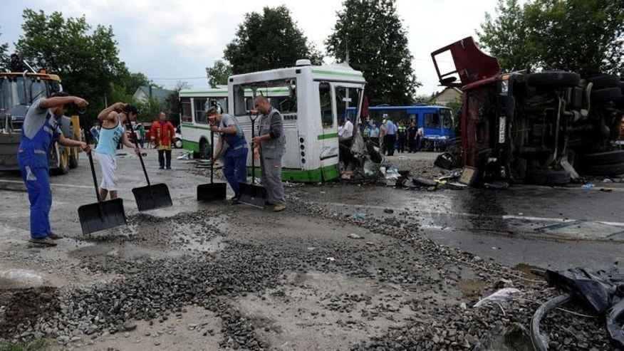 Men clear the crash scene near the village of Oznobikhino, on July 13, 2013. Russian investigators have interrogated the hospitalised driver of a truck that ploughed into a packed passenger bus outside Moscow killing 18 people.