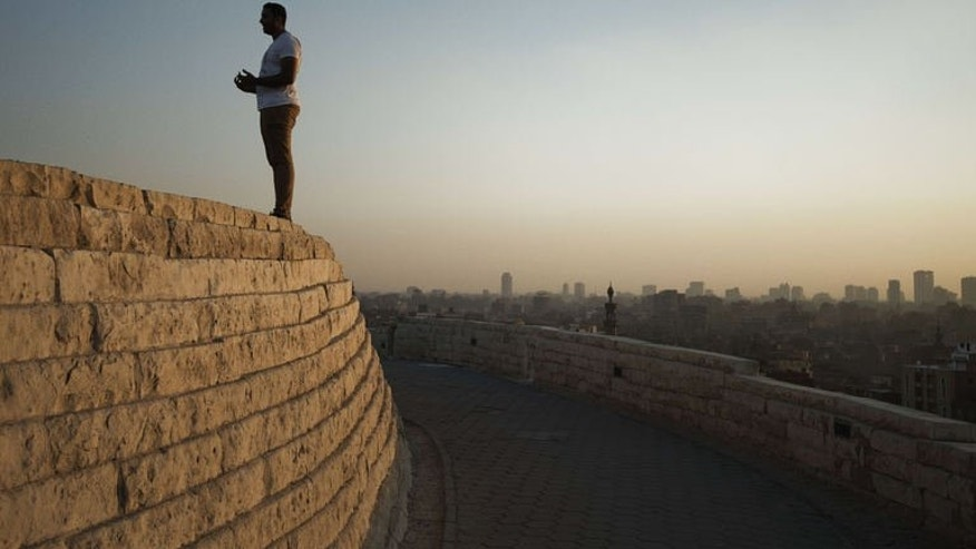 A man stands on top of a wall as the sun sets on al-Ahzar park on July 13, 2013 in Cairo. A senior US official flew into Cairo early Monday, hours after Egypt's prosecutor ordered the freezing of assets belonging to 14 top Islamists.