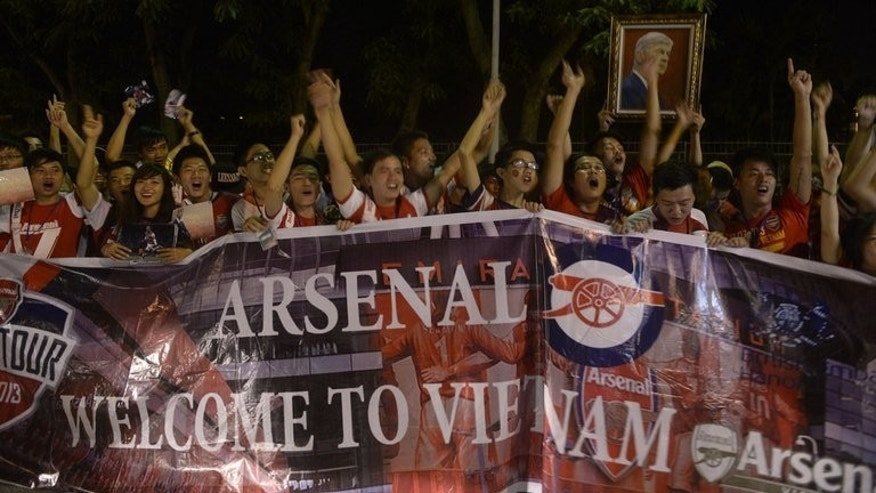 Vietnamese football fans cheer as they wait for the arrival of Arsenal players at Hanoi airport on July 15, 2013. Hundreds of cheering Vietnamese football fans turned out to greet Arsenal as they became the first English Premier League club to visit the football-mad communist country.