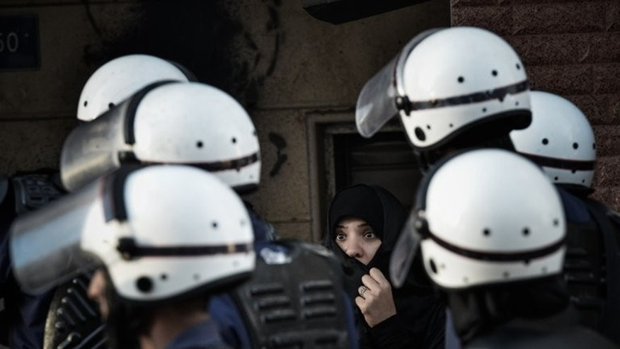 Bahraini police officers walk past a woman in Manama on January 18, 2013. Assailants hurled firebombs at the home of a Shiite lawmaker in Bahrain, without causing any casualties even though his family was inside at the time, parliament said.