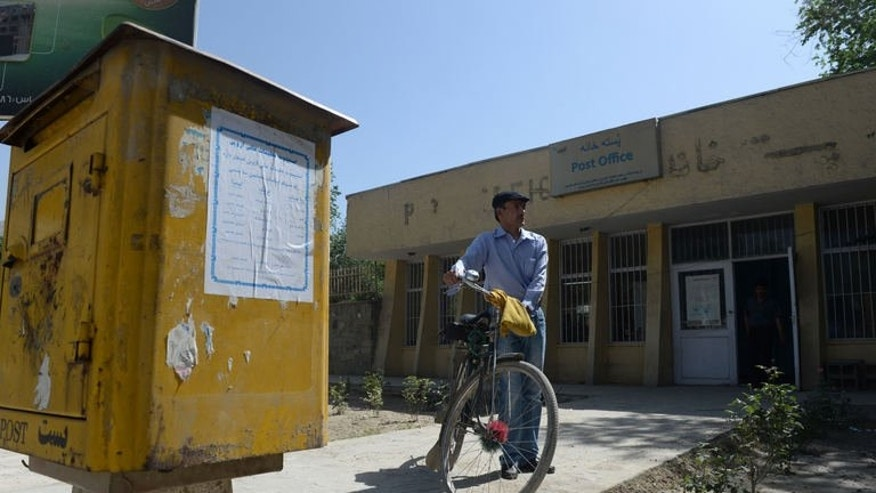 Afghan postman Mohammad Rahim leaves his post office to deliver letters in the Kart-e-Sakhi neighbourhood of Kabul on June 11, 2013. Rahim makes his rounds on the tattered, hilly streets of the Afghan capital riding an old bicycle. After 10 years on the job he is undaunted by even the vaguest addresses on letters.