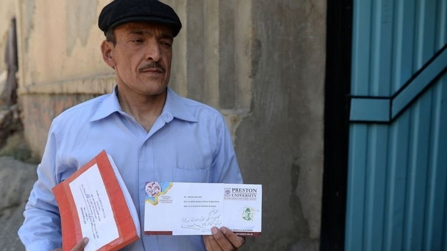 Afghan postman Mohammad Rahim holds letters for delivery in the Kart-e-Sakhi neighbourhood of Kabul on June 11, 2013. Rahim delivers dozens of letters every day across west and southwest Kabul, a city reduced almost to ruins in the brutal 1992-96 civil war.