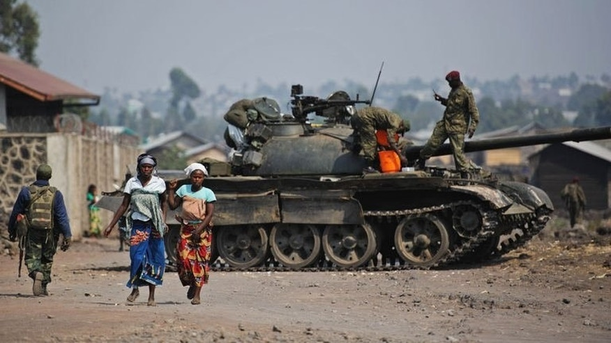 Two women walk past a government army tank in Munigi, on the outskirts of Goma in the east of the Democratic Republic of the Congo on July 15, 2013. At least 130 people have been killed, including 10 soldiers, in ongoing clashes between army forces and rebels in eastern Democratic Republic of Congo, the government said Monday.