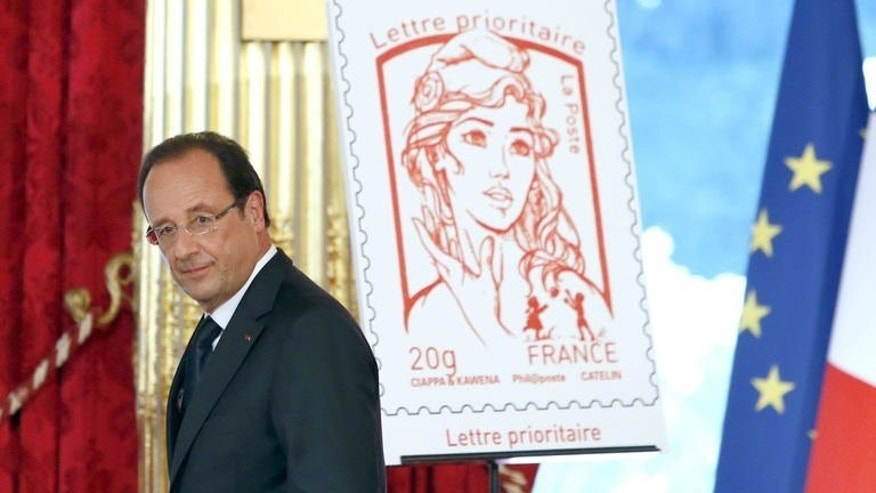 French President Francois Hollande walks past the new stamp featuring Marianne, the symbol of the French republic, after unveiling it at the presidential Elysee Palace in Paris during Bastille Day celebrations on July 14, 2013. The new stamp emblazoned with the face of Marianne has caused a stir after its creator said it was inspired by a Ukrainian feminist known for topless protests.