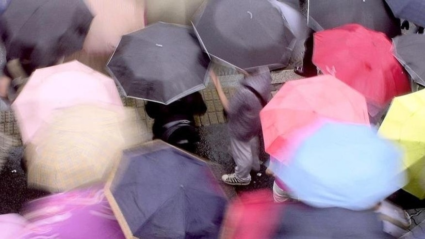 South Koreans carry colorful umbrellars as they cross a street in Seoul, on May 28, 2004. Three South Koreans have been confirmed dead or missing after heavy rains pounded the Korean peninsula, leaving hundreds homeless as the downpours left a trail of destruction in the two Koreas.