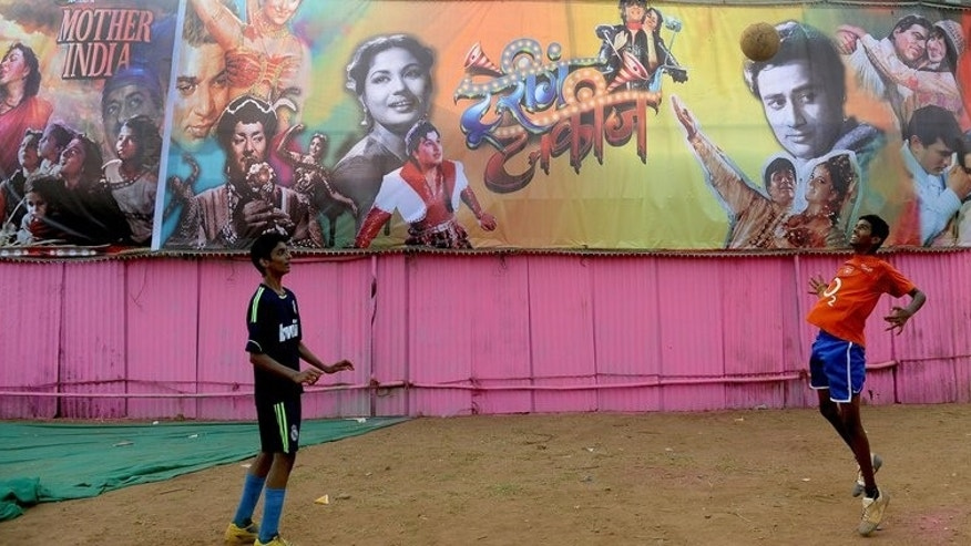 Two boys play football in central Mumbai on April 19, 2013. India's top football clubs have hit out at the national federation over moves to stage a cash-rich franchise-based tournament inspired by cricket's popular Indian Premier League early next year.