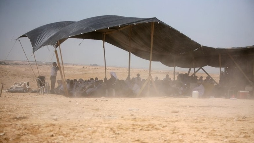 Bedouins attend Friday prayer under a tent in the Al-Araqib village located between Beersheba and Rahat in the Israeli Negev desert on May 14, 2010. Israeli police said they detained 15 Bedouin as hundreds of the tribesmen and women marched in the city of Beersheba to protest a government plan to resettle them.