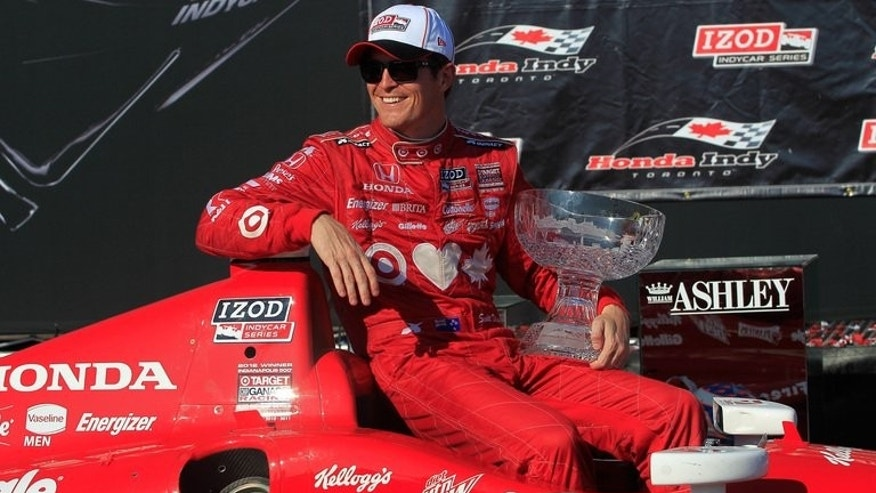 Scott Dixon poses with the trophy on July 14, 2013 after dominating Toronto's IndyCar street circuit. Dixon, who won last weekend's race in Pocono, captured his third victory in a row and 32nd career title.