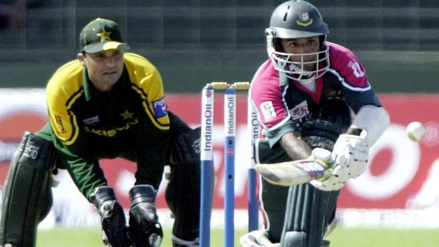 Bangladesh batsman Rajin Saleh sweeps a ball as Pakistan wicketkeeper Moin Khan (left) looks on during a match in Colombo on July 17, 2004. Pakistan's cricket bosses appointed former captain Khan as chief selector, a post he said he took on as a challenge.