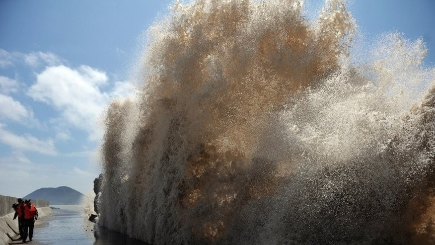 Huge waves surge up against the shoreline of Diaobin fishing port in Wenling, eastern China, on July 12, 2013. At least 295 people have been confirmed dead or missing after rainstorms and Typhoon Soulik hit China, causing floods, landslides and buildings to collapse.