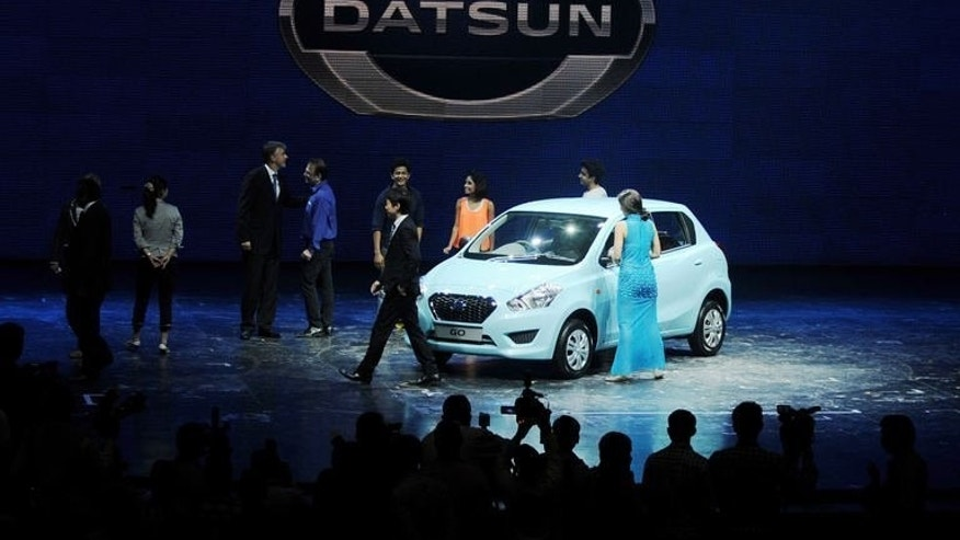 Performers and officials stand around during the launch of the Datsun Go car at a function in Gurgaon on the outskirts of New Delhi on July 15, 2013. Japanese carmaker Nissan resurrected its iconic budget Datsun marque on Monday to woo a new generation of cost-conscious buyers in emerging markets.