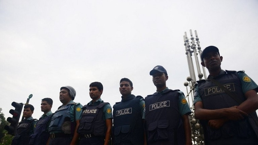 Police stand guard during a nationwide strike called by the Islamist political party, Jumaat-e-Islami, in Dhaka, on May 14, 2013. Police fired rubber bullets at protesters on Monday, as violence erupted across the country ahead of the verdict on a top Islamist for allegedly masterminding atrocities during the 1971 liberation war.