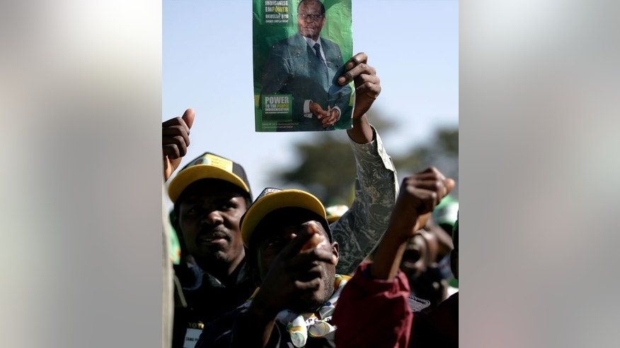 Supporters of Zimbabwean president Robert Mugabe's party ZANU-PF wave a picture of their leader during a party rally on July 15, 2013 in Marondera, Zimbabwe. Though Mugabe appears vibrant and puffed up on his campaign posters, his slow step and demeanour tell a different story, adding to speculation about the health of Zimbabwe's most influential politician.