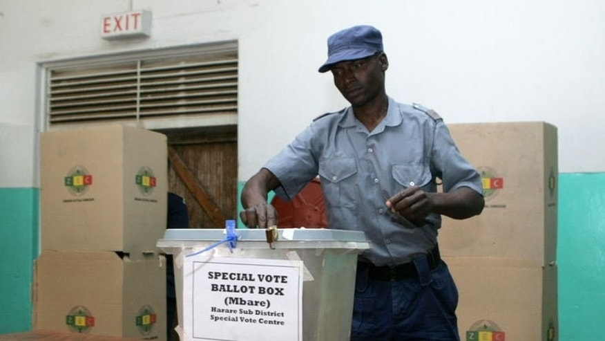 A police officer casts his ballot during the special voting day for the police and army in Harare on July 14, 2013. On July 31 Zimbabweans will go to the polls to elect a president. One name, a permanent feature on ballot papers since independence in 1980, will again appear, Robert Gabriel Mugabe.