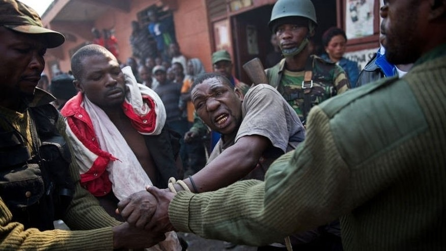 A man accused by the Congolese army of being a spy of rebels of the M23 movement is tied and taken away on July 16, 2013 in Munigi on the outskirts of Goma. The army in DR Congo on Tuesday pursued an offensive against rebels of the M23 movement to protect the North Kivu provincial capital of Goma, military sources said.