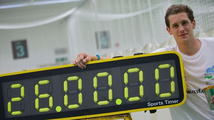 Alby Shale poses next to a timer after batting for 26 hours at the Oval cricket club in London, on July 16, 2013. He beat the previous world record of 25 hours, set in October by Australian batsman Jade Child.