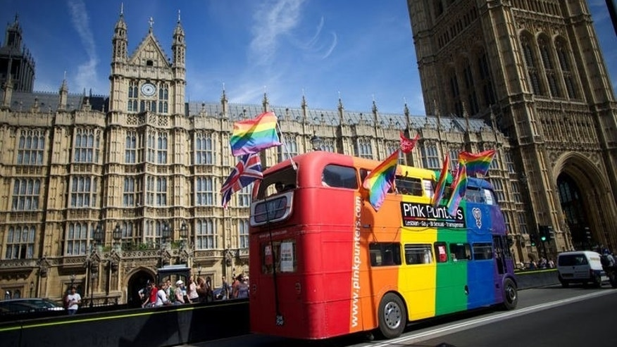 Gay campaigners drive a bus past the Houses of Parliament in central London on July 15, 2013. Civil partnerships for gay couples have been legal in Britain since 2005, giving them identical rights and responsibilities to straight couples in a civil marriage.