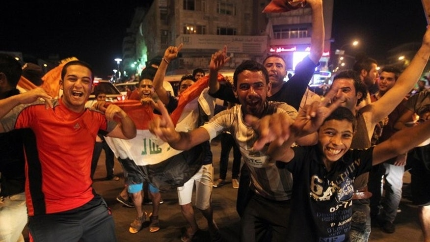 Iraqis celebrate in the streets of Baghdad after their side beat South Korea in the Under-20 World Cup quarter-finals on July 7, 2013. Security and medical officials said at least four people were killed and around 21 wounded by gunfire after the match.