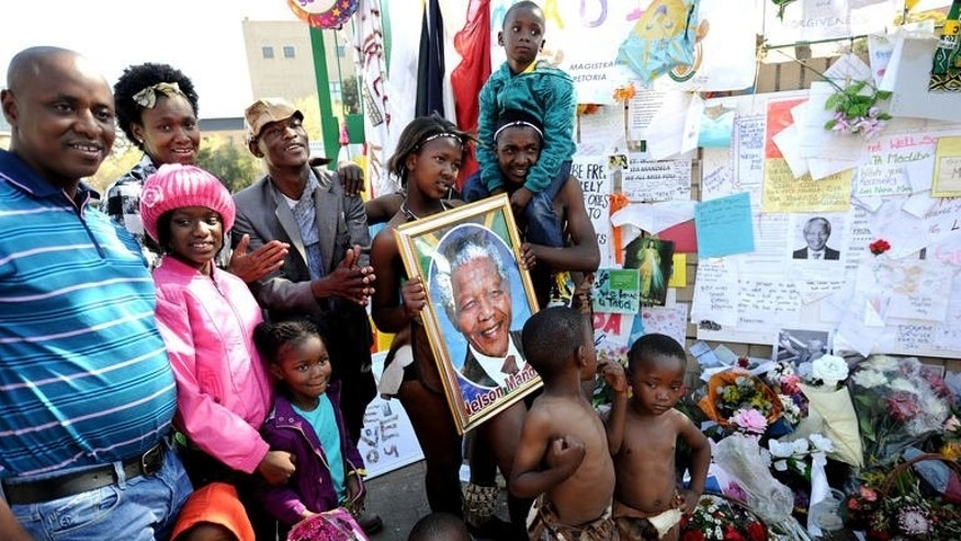 People pose in front of tributes for former South African president Nelson Mandela outside the Medi Clinic Heart Hospital in Pretoria, on July 14, 2013. Criticism of Mandela is rare in South Africa, much less so when he is lying in a hospital bed.The 94-year-old's opposition to apartheid have won him worldwide, but not, it seems, universal adoration.