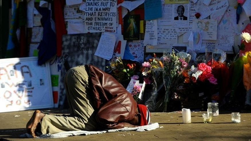 A man prays for former South African president Nelson Mandela outside the MediClinic Heart Hospital in Pretoria, on July 15, 2013.