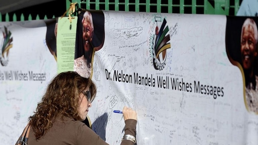 A woman writes a message on a wall covered with tributes to Nelson Mandela in Pretoria, July 14, 2013. Twenty years after those talks, some still believe the deal he struck with South Africa's white rulers ensured blacks would be disenfranchised for decades to come.