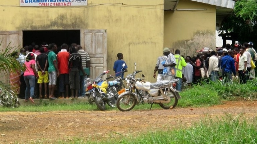 People stand in front of a tribunal in Ambam, Cameroon, during a homosexuality trial on March 15, 2012. A gay rights campaigner in Cameroon was found dead in his Yaounde home after being tortured, Human Rights Watch said on Tuesday.