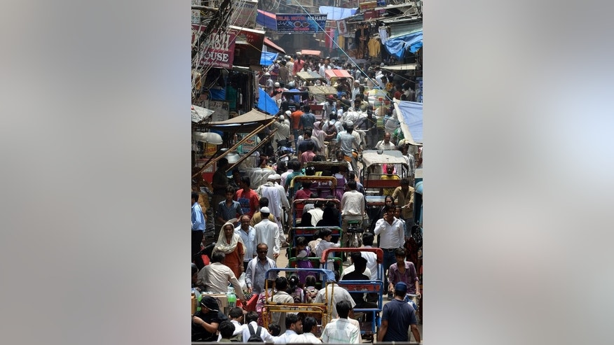 Indian commuters travel through a market area of New Delhi on July 10, 2013. India's rupee has been the worst performing major Asian currency this financial year, dropping to a record low of 61.20 to the dollar last week.