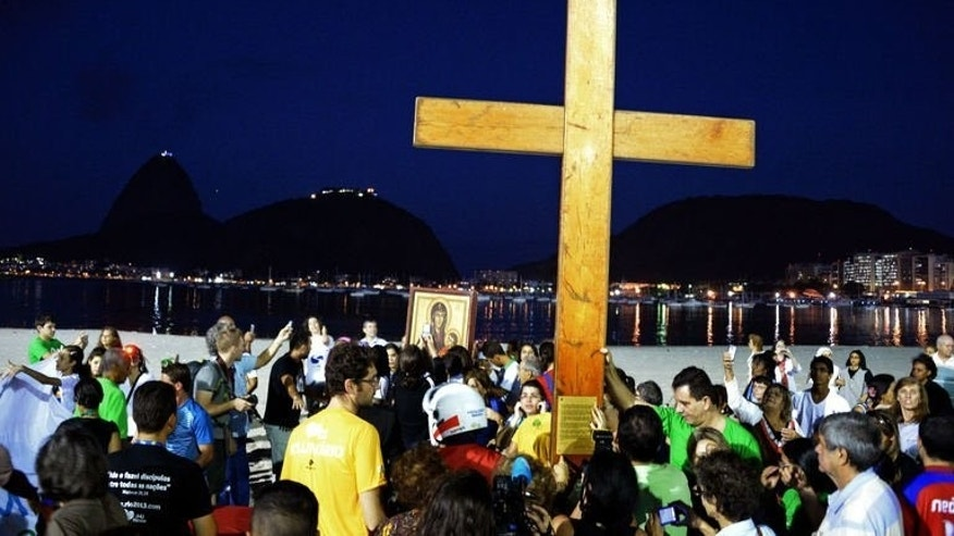 Catholics carry the World Youth Day Cross that in 1984 Pope John Paul II entrusted the youth of the world, at Botafogo beach in Rio de Janeiro on July 15, 2013. The Pope is due in Rio for the July 22-28 Catholic event, which is expected to attract two million people from around the globe.