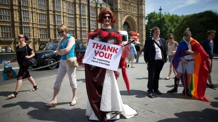 Gay campaigners rally outside the Houses of Parliament on July 15, 2013. MPs on Tuesday passed a bill legalising same-sex marriage in England and Wales, paving the way for the first gay weddings in 2014.