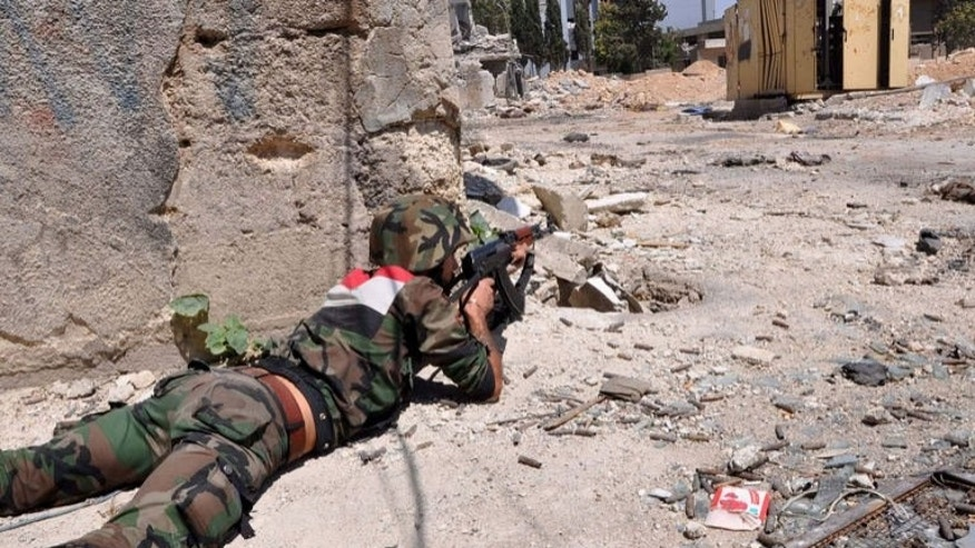 Syrian government soldiers take position during a patrol near Al-Manashir roundabout in Jobar in the outskirts of Damascus on July 14, 2013. At least nine Syrians, including a child, were executed by regime forces at a checkpoint in Damascus province, a watchdog said on Tuesday.