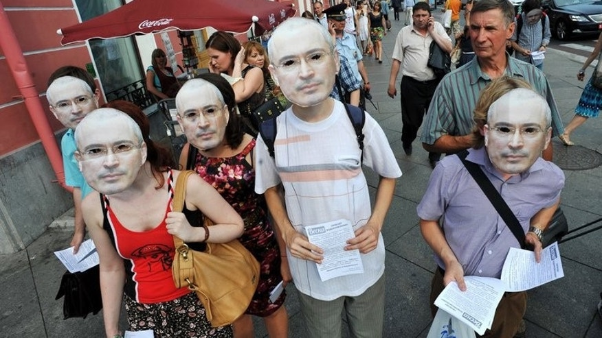Opposition activists wear masks of the jailed tycoon Mikhail Khodorkovsky during a rally in St. Petersburg on June 26, 2013. Khodorkovsky was convicted on what he says were politically motivated charges.
