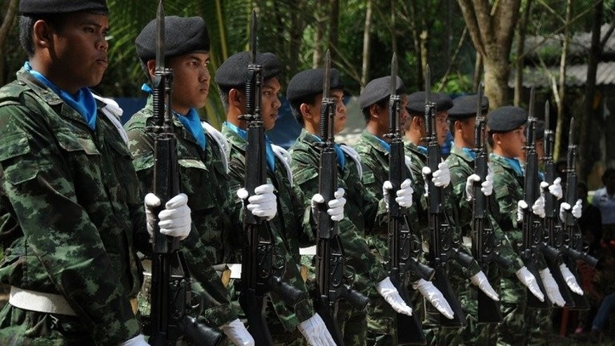 Thai soldiers raise their rifles during the funeral ceremony of a Muslim Ranger killed in an attack by suspected separatist militants in the restive southern province of Narathiwat, on June 20, 2013. Thailand is considering reducing the number of troops in its insurgency-riven south if a lull in violence holds, the deputy prime minister said on Tuesday.